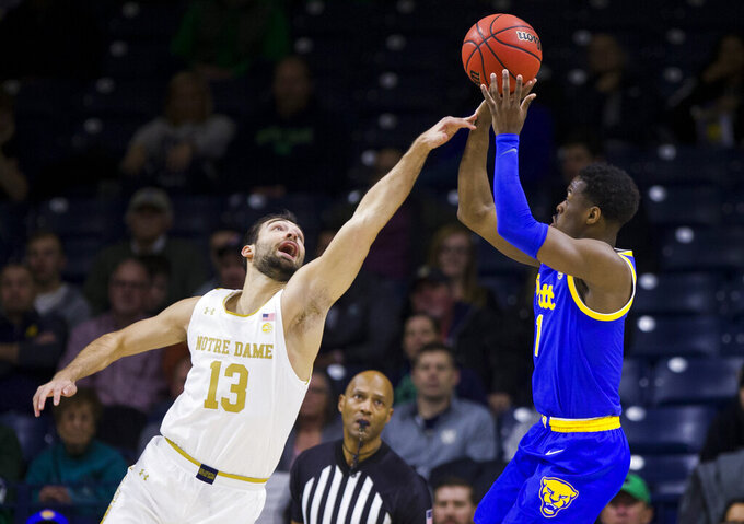 Notre Dame's Nikola Djogo (13) fouls Pittsburgh's Xavier Johnson as he shoots during the first half of an NCAA college basketball game Wednesday, Feb. 5, 2020, in South Bend, Ind. (AP Photo/Robert Franklin)