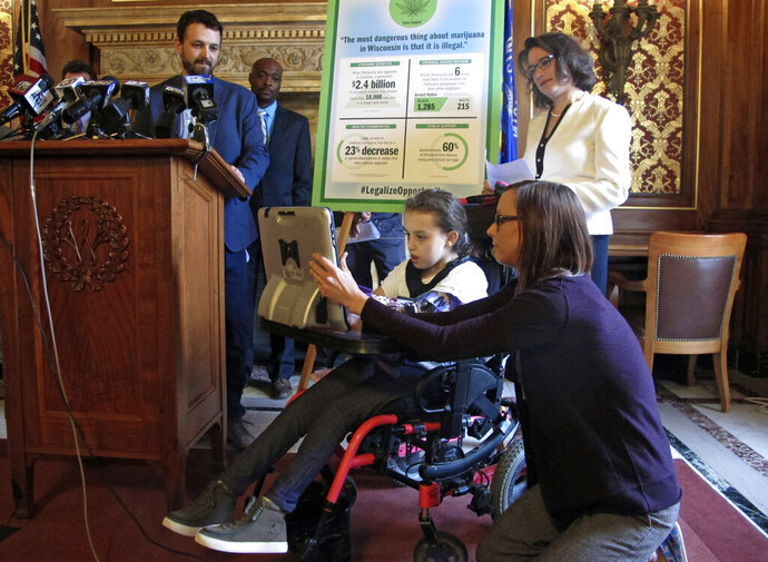 Norah Lowe, 10, speaks through a computer in favor of legalizing medical marijuana with her mother, Megan, at her side while her dad, Josh, stands at the podium and state Rep. Melissa Sargent watches on Thursday, April 18, 2019, in Madison, Wisc. The Lowes and others attended a news conference announcing Sargent's latest attempt in the Wisconsin Legislature to legalize marijuana. (AP Photo/Scott Bauer)