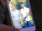FILE - In this July 4, 2018, file photo, the aunt of coach Ekapol Chanthawong shows a picture of the coach and his grandmother on a mobile phone screen, in Mae Sai, Chiang Rai province, in northern Thailand. The day-to-day pearls of wisdom imparted by coaches to players _ from little league, to high school, to college and even the pros _ are rarely all that groundbreaking: Try your hardest, don't lose focus, support your teammates, keep your chin up. In the case of 12 youth soccer players trapped in a cave in Thailand, it helped save their lives. (AP Photo/Sakchai Lalit, File)