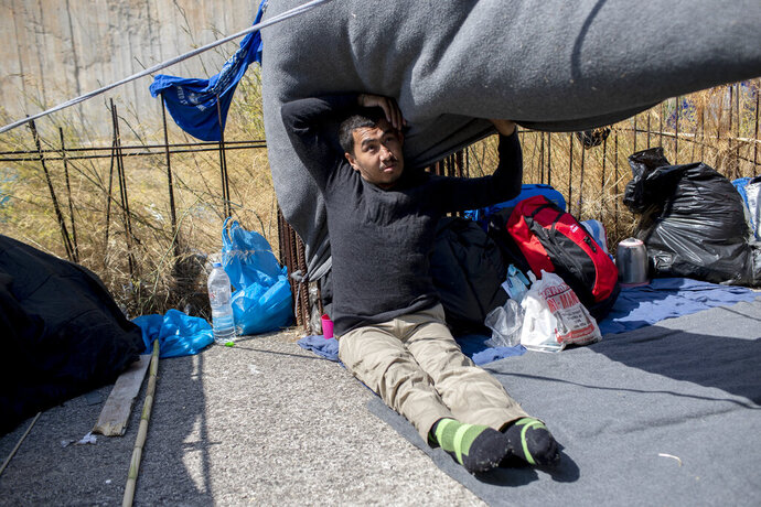 Homeless Afghan refugee Ayoub Husseini, who has lost the use of his legs after a construction accident, sits on a blanket with his belongings on the terrace of a commercial building on the island of Lesbos. Greece, Monday, Sept. 14, 2020.  Ayoub who hopes to receive medical treatment for his injuries in Europe, is one of thousands of asylum-seekers left homeless after a fire gutted Moria refugee camp on the island. (AP Photo/Petros Giannakouris)