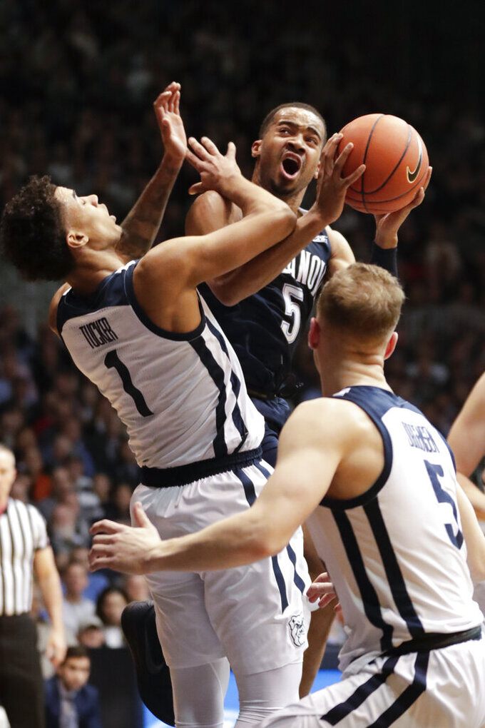 Villanova guard Phil Booth (5) is fouled as he shoots by Butler forward Jordan Tucker (1) in the first half of an NCAA college basketball game in Indianapolis, Tuesday, Jan. 22, 2019. (AP Photo/Michael Conroy)