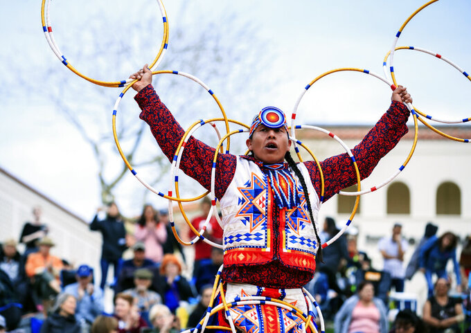 In this photo provided by the Heard Museum, Scott Sixkiller Sinquah, who is Gila River Pima, Hopi, Cherokee and Choctaw, performs at the annual Heard Museum World Championship Hoop Dance Contest in Phoenix, Feb. 9, 2020. Hoop dancing has rarely ever been about competition for the world champion Sinquah. He does it to pay homage to traditional healing aspects of the dancing the style is known for. He also dances for his fellow dancers and that friendly connection that's been missing since the pandemic hit. (Jared Platt/Heard Museum via AP)