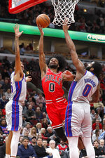 Chicago Bulls' Coby White (0) shoots between Detroit Pistons' Christian Wood, left, and Andre Drummond during the second half of an NBA basketball game Wednesday, Nov. 20, 2019, in Chicago. The Bulls won 109-89.(AP Photo/Charles Rex Arbogast)