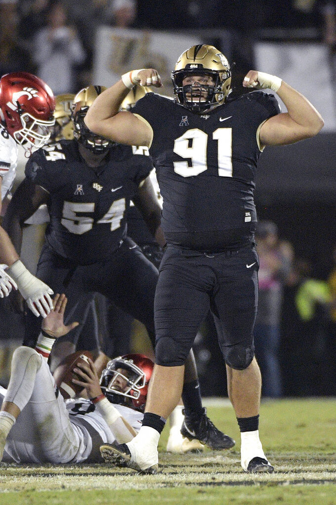 Central Florida defensive lineman Joey Connors (91) celebrates after sacking Cincinnati quarterback Desmond Ridder (9) during the first half of an NCAA college football game Saturday, Nov. 17, 2018, in Orlando, Fla. (AP Photo/Phelan M. Ebenhack)