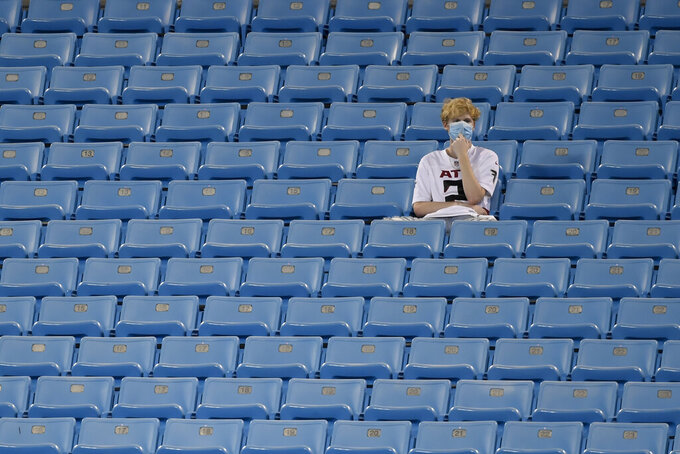 A Atlanta Falcons fan watches during warm ups before an NFL football game between the Carolina Panthers and the Atlanta Falcons Thursday, Oct. 29, 2020, in Charlotte, N.C.. (AP Photo/Mike McCarn)