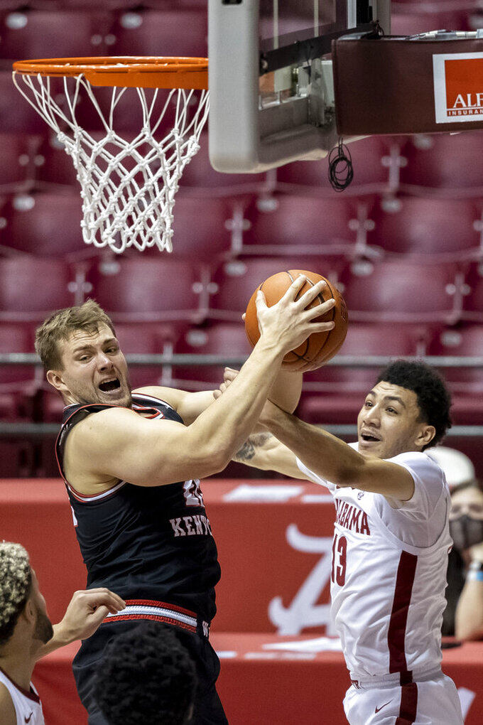 Western Kentucky forward Carson Williams (22) grabs rebound under pressure from Alabama guard Jahvon Quinerly (13) during the first half of an NCAA college basketball game, Saturday, Dec. 19, 2020, in Tuscaloosa, Ala. (AP Photo/Vasha Hunt)