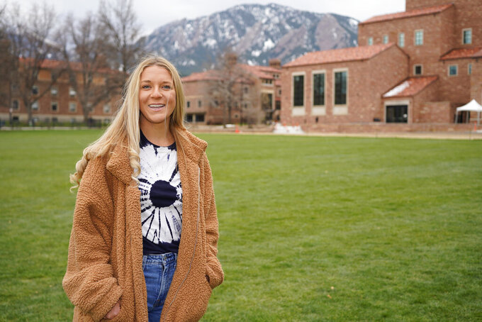 In this April 23, 2021, photo Sydney Kramer, a graduate student at the University of Colorado, poses for a photo on the campus in Boulder, Colo. Kramer is typical of many new Colorado arrivals. The 23-year-old moved to the university town of Boulder in January to begin graduate studies in atmospheric and oceanic sciences. She could have stayed in Miami, a natural location for someone of her interests and where she finished her undergraduate studies. But Kramer was depressed by Florida's anti-science turn under Republican state control. (AP Photo/David Zalubowski)