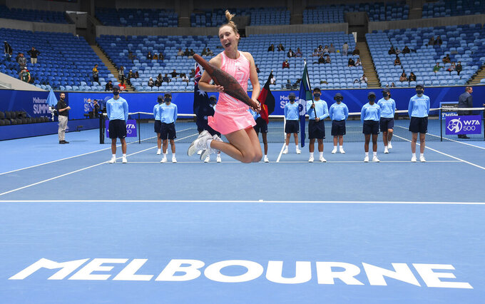 Belgium's Elise Mertens leaps as she holds her trophy after defeating Estonia's Kaia Kanepi in the final of the Gippsland Trophy in Melbourne, Australia, Sunday, Feb. 7, 2021.(AP Photo/Andy Brownbill)