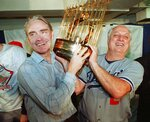 FILE - Los Angeles Dodgers manager Tommy Lasorda, right, and Fred Claire, Dodger Vice President, hoist the World Series trophy following their team's 5-2 win over the Oakland Athletics in Oakland, Calif., in this Oct. 20, 1988, file photo. Lasorda, the fiery Hall of Fame manager who guided the Los Angeles Dodgers to two World Series titles and later became an ambassador for the sport he loved during his 71 years with the franchise, has died. He was 93. The Dodgers said Friday, Jan. 8, 2021, that he had a heart attack at his home in Fullerton, California.  (AP Photo/File)