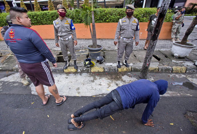 Public Order Agency officers watch as a man does push ups as a punishment for violating city regulation requiring people to wear face mask in public places as a precaution against the new coronavirus outbreak, in Medan, North Sumatra, Indonesia, Wednesday, Aug. 12, 2020. (AP Photo/Binsar Bakkara)