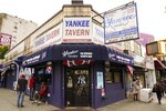 Pedestrians pass the Yankee Tavern, Friday, Aug. 14, 2020, in New York. The tavern has been in business since 1927. The coronavirus pandemic has been especially hard on businesses that rely on ballpark traffic, eliminating crowds at major league games, and leading to rules that limit the amount of people they can have inside their doors at the same time. (AP Photo/Frank Franklin II)