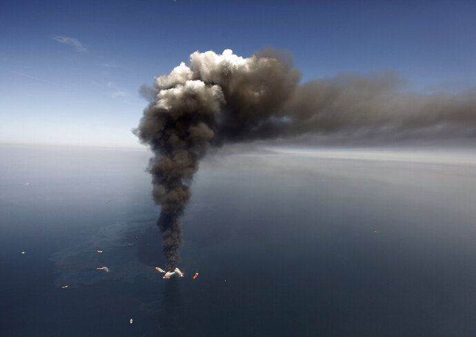 FILE - In this April 2010 file photo, oil can be seen in the Gulf of Mexico, more than 50 miles southeast of Venice on Louisiana's tip, as a large plume of smoke rises from fires on BP's Deepwater Horizon offshore oil rig. Federal agencies have approved $225 million in settlement money from the BP oil spill for 18 projects to restore the open ocean. The projects are described in a 490-page report released Tuesday, Dec. 10, 2019. (AP Photo/Gerald Herbert, File)