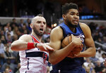 Minnesota Timberwolves center Karl-Anthony Towns, right, grabs a rebound in front of Washington Wizards center Marcin Gortat, from Poland, during the second half of an NBA basketball game, Tuesday, March 13, 2018, in Washington. The Timberwolves won 116-111. (AP Photo/Alex Brandon)