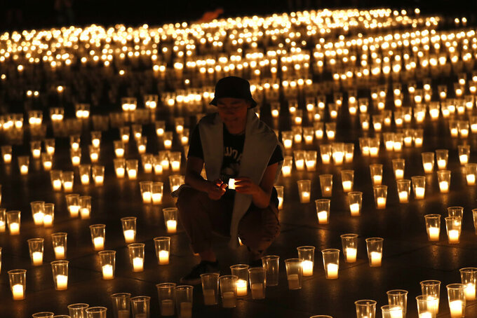 A man lights up candles to commemorate victims of the COVD-19 pandemic at the Prague Castle in Prague, Czech Republic, Monday, May 10, 2021. The Czech Republic is massively relaxing its coronavirus restrictions as the hard-hit nation pays respect to nearly 30,000 dead. (AP Photo/Petr David Josek)