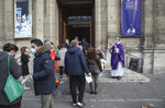 Priest Antoine d'Eudeville, right, wearing a face mask as a precaution against the coronavirus welcomes church-goers as they lineup at the entrance of the Notre-Dame-des-Champs church in Paris, Sunday, Nov. 29, 2020. French churches, mosques and synagogues can open their doors again to worshippers - but only a few of them, as France cautiously starts reopening after a second virus lockdown. Some churches may defy the 30-person limit they feel as too unreasonable, and other sites may stay closed until they can reopen for real. (AP Photo/Michel Euler)