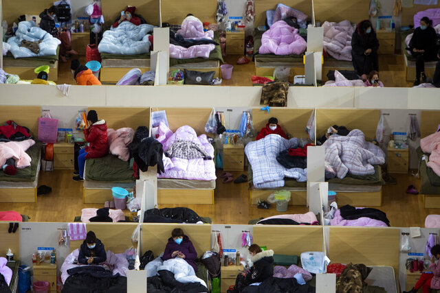 In this Monday, Feb. 17, 2020, photo released by Xinhua News Agency, patients infected with the coronavirus take rest at a temporary hospital converted from Wuhan Sports Center in Wuhan in central China's Hubei Province. China reported thousands new virus cases and more deaths in its update Tuesday on a disease outbreak that has caused milder illness in most people, an assessment that promoted guarded optimism from global health authorities. (Xiao Yijiu/Xinhua via AP)