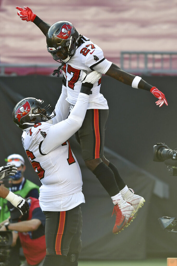 Tampa Bay Buccaneers running back Ronald Jones (27) gets a lift from offensive tackle Donovan Smith (76) after scoring against the Green Bay Packers during the first half of an NFL football game Sunday, Oct. 18, 2020, in Tampa, Fla. (AP Photo/Jason Behnken)