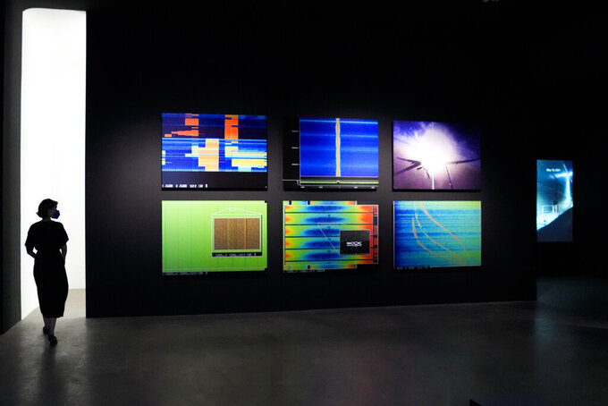 """A woman walks through an exhibition by American artist and filmmaker Laura Poitras, near the art work """"Anarchist"""" by Laura Poitras in collaboration with Henrik Moltke, at the N.K.B. gallery in Berlin, Germany, on Friday, June 18, 2021. The exhibition by Poitras, known for her award-winning 2014 documentary on former U.S. intelligence contractor Edward Snowden, is on display at the gallery until Aug. 8, 2021. (AP Photo/Markus Schreiber)"""