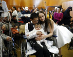In this Wednesday, Nov. 27, 2019 photo,  Javier Rodriguez and Crystal Cuevas hold their four-month-old daughter Leia as they celebrate during their wedding before family, friends and medical staff in the chapel at the University of Chicago Medical Center for Care and Discovery in Chicago. Rodriguez, 23, who received two heart transplants as a teenager died in hospice care, days after he married his high school sweetheart, his new bride said.  (Brian Cassella/Chicago Tribune via AP)