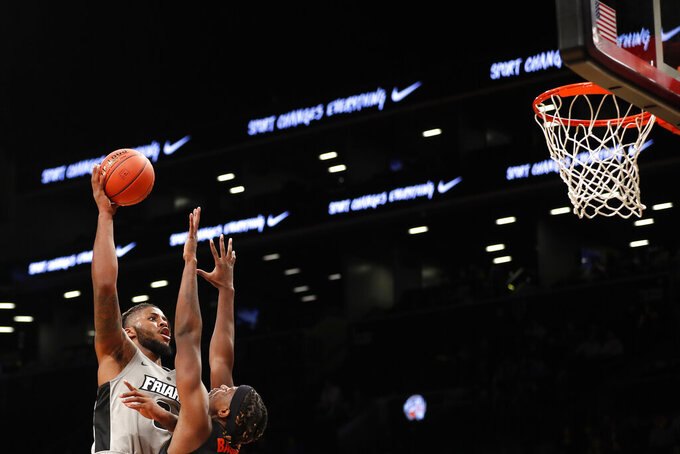 Providence center Nate Watson (0) shoots over Florida forward Dontay Bassett during the second half of an NCAA college basketball game at Barclays Center, Tuesday, Dec. 17, 2019, in New York. (AP Photo/Michael Owens)