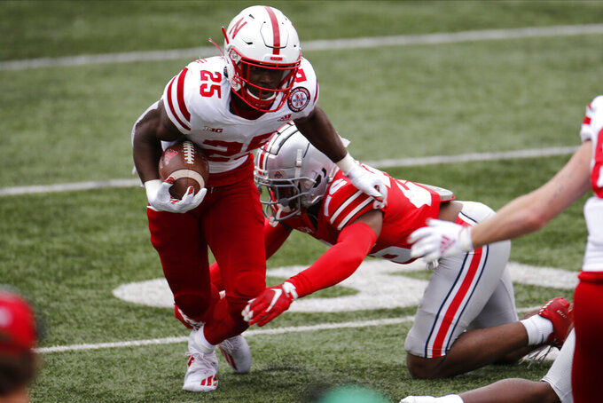 Nebraska running back Ronald Thompkins, left, runs past Ohio State defensive back Lloyd McFarquhar during the second half of an NCAA college football game Saturday, Oct. 24, 2020, in Columbus, Ohio.  (AP Photo/Jay LaPrete)