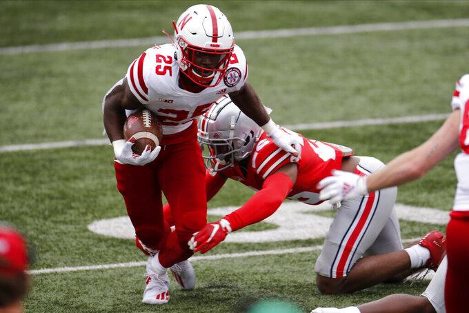 Nebraska running back Ronald Thompkins, left, runs past Ohio State defensive back Lloyd McFarquhar during the second half of an NCAA college football game Saturday, Oct. 24, 2020, in Columbus, Ohio.  (AP Photo/Jay LaPrete)