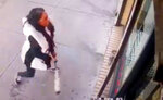 In this Jan. 15, 2019 image taken from surveillance video, a woman smashes the windows of