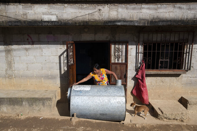 Alvina Jeronimo Perez places a storage container for ears of corn in the sun outside her home after washing it in Tizamarte, Guatemala, Wednesday, Dec. 9, 2020. After a failed crossing into the U.S. in March 2020, Jeronimo's house is her only refuge, but she owes money that paid for the smuggler and the lender now demands payment or her house. (AP Photo/Moises Castillo)