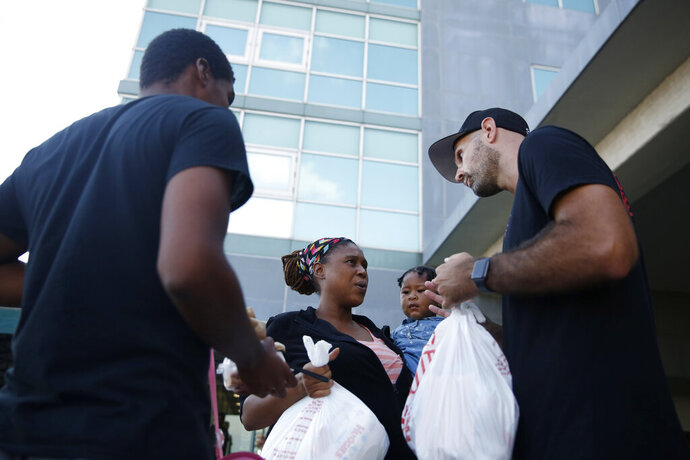 Volunteer Nick Mills, right, hands Hurricane Dorian evacuee, Leshonda Collins and her 1-year-old daughter Shayniyah, supplies as they arrive from the Grand Celebration cruise ship from Freeport, a city in the Grand Bahamas on Wednesday, Sept. 18, 2019 in Riviera Beach. The cruise ship transported hundreds of evacuees seeking passage from Freeport after the damaged caused by Hurricane Dorian.
