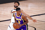 Denver Nuggets' Jamal Murray (27) falls back as he defends against Los Angeles Lakers' Rajon Rondo (9) during the first half of an NBA conference final playoff basketball game Saturday, Sept. 26, 2020, in Lake Buena Vista, Fla. (AP Photo/Mark J. Terrill)