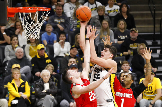 Iowa center Luka Garza (55) drives to the basket between Ohio State's Kyle Young, left, and Luther Muhammad, right, during the second half of an NCAA college basketball game, Thursday, Feb. 20, 2020, in Iowa City, Iowa. Iowa won 85-76. (AP Photo/Charlie Neibergall)