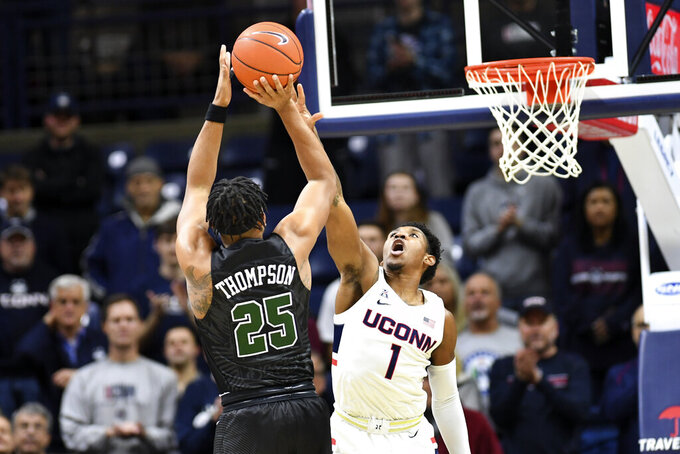 Connecticut's Christian Vital (1) tries to block a shot by Tulane's Christion Thompson (25) in the first half of an NCAA college basketball game Wednesday, Jan. 8, 2020, in Storrs, Conn. (AP Photo/Stephen Dunn)