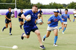 Russia's Vladimir Podrezov runs with local high school students during a rugby clinic in Saitama, north of Tokyo, Sunday, Sept. 15, 2019.  (Yuki Sato/Kyodo News via AP)