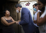 FILE - In this Dec. 10, 2020 file photo, Venezuelan opposition leader Juan Guaidó talks with a resident during a visit to La Lucha neighborhood of Caracas, Venezuela, amid the new coronavirus pandemic. The opposition led by Guaidó, who the U.S. recognizes as Venezuela's rightful president, says President Nicolas Maduro can't be trusted to distribute the vaccine in a country where the coronavirus pandemic has been used as a cover for human rights abuses. (AP Photo/Ariana Cubillos, File)