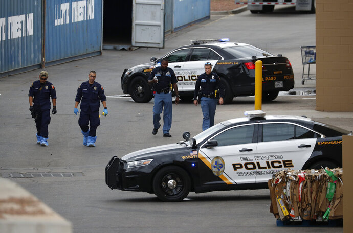 FILE - In this Aug. 6, 2019, file photo, police officers walk behind a Walmart at the scene of a mass shooting at a shopping complex in El Paso, Texas. Patrick Crusius, 21, was indicted Thursday, Sept. 12, 2019, for capital murder in connection with the Aug. 3 mass shooting that left 22 dead. He is jailed without bond. (AP Photo/John Locher, File)