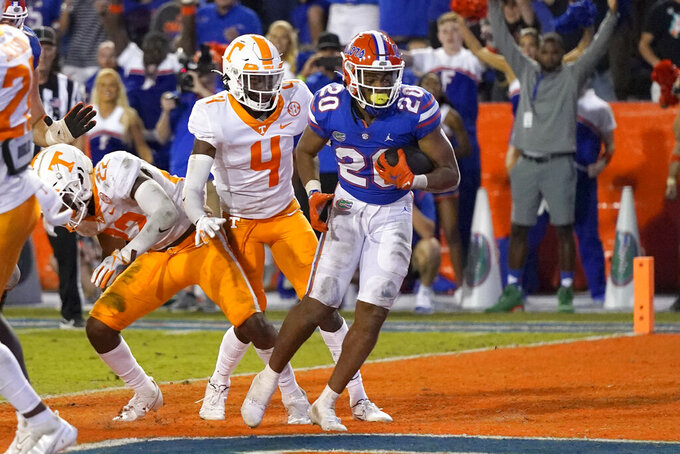 Florida running back Malik Davis (20) runs past Tennessee defensive backs Jaylen McCollough, left, and Warren Burrell (4) to score a touchdown during the second half of an NCAA college football game, Saturday, Sept. 25, 2021, in Gainesville, Fla. (AP Photo/John Raoux)