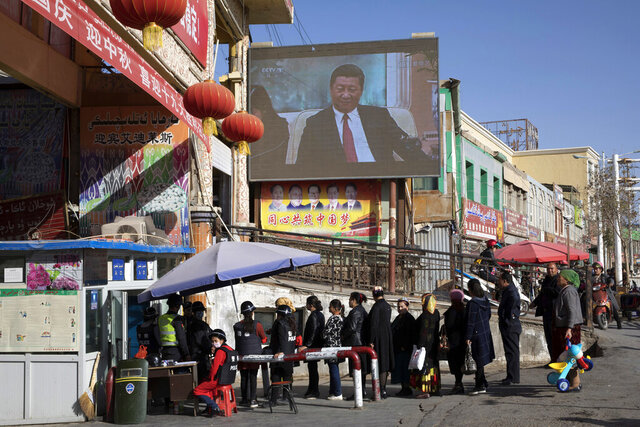 FILE - In this Nov. 3, 2017, file photo, residents line up at a security checkpoint into the Hotan Bazaar where a screen shows Chinese President Xi Jinping in Hotan in western China's Xinjiang region. The U.S. government has imposed trade sanctions on 11 companies it says are implicated in human rights abuses in China's Muslim northwestern region of Xinjiang.(AP Photo/Ng Han Guan, File)