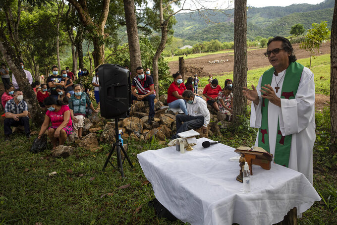 Friar Leopoldo Serrano celebrates an outdoor Mass at Mission San Francisco de Asis, in Honduras, Sunday, June 27, 2021. The pastor of souls has turned into a project manager and construction foreman for the families of La Reina, a nearby Honduran village buried in an epic mudslide in November 2020, its families among nearly half a million Central Americans displaced by Hurricanes Eta and Iota. (AP Photo/Rodrigo Abd)
