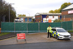 Police secure the area around the industrial estate where 39 lifeless bodies, eight women and 31 men, were discovered Wednesday in a truck, near Grays, southeast England, Friday Oct. 25, 2019.  China called Friday for joint efforts to counter human smuggling after the discovery in Britain of 39 dead people believed to be Chinese who stowed away in a shipping container. (Kirsty O'Connor/PA via AP)