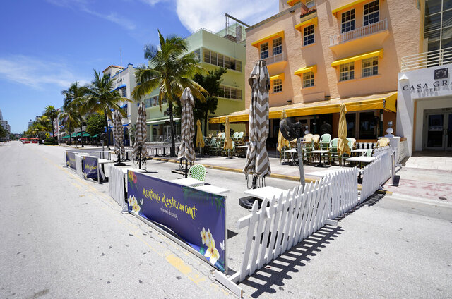 Empty outdoor seating for a restaurant and closed hotels are shown, Tuesday, Aug. 11, 2020, in Miami Beach, Florida's famed Ocean Drive on South Beach. Florida added 276 fatalities to its coronavirus death toll on Tuesday, a new state record. (AP Photo/Wilfredo Lee)