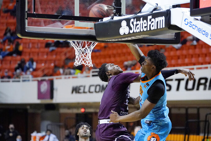 Oklahoma State forward Matthew-Alexander Moncrieffe, right, dunks over Texas Southern forward Joirdon Karl Nichols during the second half of an NCAA college basketball game in Stillwater, Okla., Saturday, Nov. 28, 2020. (AP Photo/Sue Ogrocki)