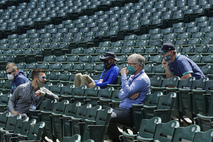 FILE - Seattle Mariners general manager Jerry Dipoto, second from left, manager Scott Servais, right, and team president and CEO Kevin Mather, second from right, watch from the stands during baseball practice in Seattle, in this July 8, 2020, file photo. Seattle Mariners general manager Jerry Dipoto and manager Scott Servais are doing damage control with players who were directly mentioned or referenced by former team CEO Kevin Mather in an online video that led to his resignation. (AP Photo/Ted S. Warren, File)