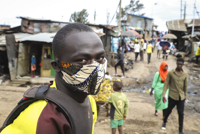 A boda-boda, or motorcycle taxi, driver wears a makeshift mask made from a local fabric known as Kitenge as he looks for customers in the Kibera neighbourhood of Nairobi, Kenya Friday, March 20, 2020. For most people, the new coronavirus causes only mild or moderate symptoms such as fever and cough and the vast majority recover in 2-6 weeks but for some, especially older adults and people with existing health issues, the virus that causes COVID-19 can result in more severe illness, including pneumonia. (AP Photo/Patrick Ngugi)
