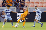 Houston Dynamo midfielder Joe Corona, middle, loses the ball between Sporting Kansas City defender Jaylin Lindsey, left, and midfielder Ilie Sanchez (6) during the first half of an MLS soccer match Wednesday, May 12, 2021, in Houston. (AP Photo/Michael Wyke)