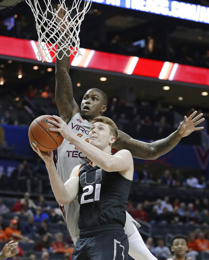 Miami's Sam Waardenburg (21) drives against Virginia Tech's Ty Outlaw (42) during the first half of an NCAA college basketball game in the Atlantic Coast Conference tournament in Charlotte, N.C., Wednesday, March 13, 2019. (AP Photo/Nell Redmond)