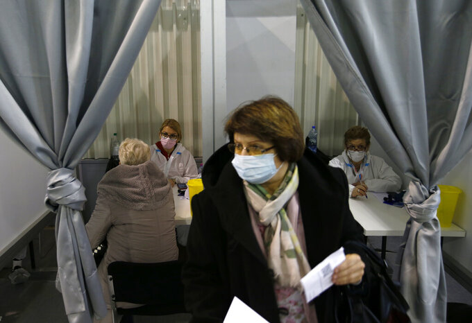 Health workers speak with people at a vaccination center in Belgrade, Serbia, Wednesday, Feb. 17, 2021. Serbia, a country of 7 million, has so far vaccinated some 1 million people, mainly with the Chinese Sinopharm vaccine and Russian Sputnik V, and to a lesser extent with the Pfizer jab. (AP Photo/Darko Vojinovic)