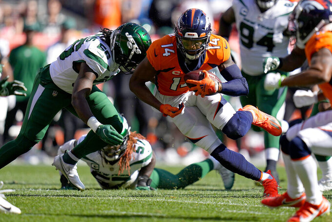Denver Broncos wide receiver Courtland Sutton (14) eludes the tackle of New York Jets defensive end Carl Lawson (58) during the first half of an NFL football game, Sunday, Sept. 26, 2021, in Denver. (AP Photo/Jack Dempsey)