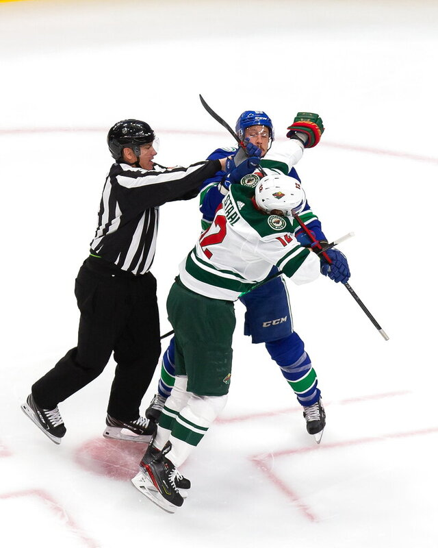 Minnesota Wild's Eric Staal (12) battles against Vancouver Canucks' Jay Beagle (83) during the first period of an NHL hockey playoff game Tuesday, Aug. 4, 2020 in Edmonton, Alberta. (Codie McLachlan/The Canadian Press via AP)