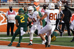 Texas' Sam Ehlinger (11) runs into the end zone for a touchdown against Baylor's Terrel Bernard (2) during the second half of an NCAA college football game in Austin, Texas, Saturday, Oct. 24, 2020. (AP Photo/Chuck Burton)
