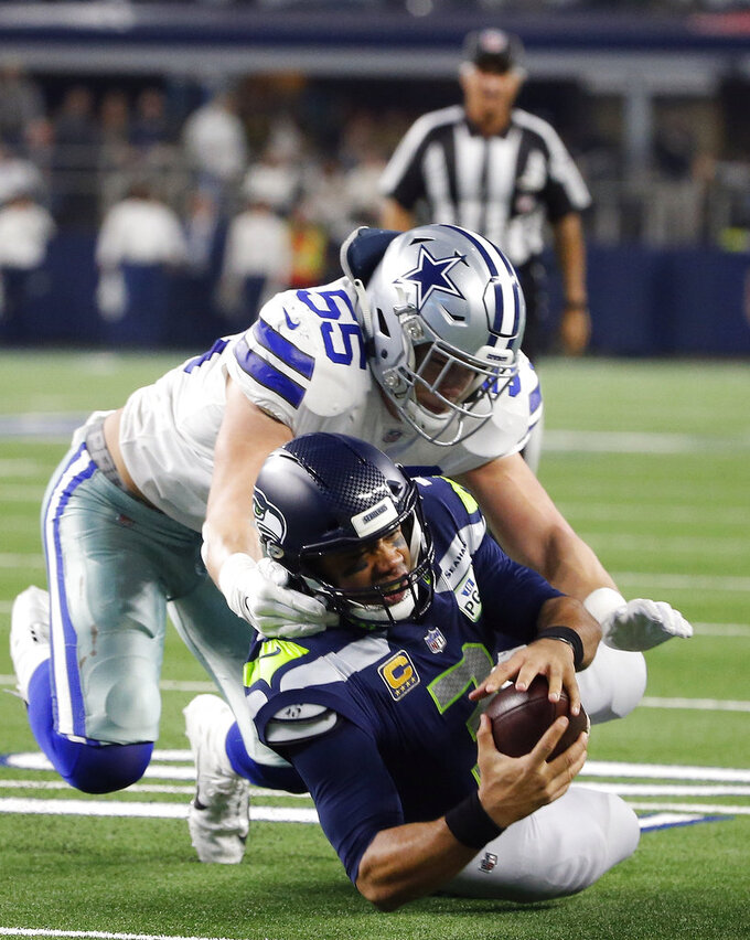 Dallas Cowboys outside linebacker Leighton Vander Esch (55) tackles Seattle Seahawks quarterback Russell Wilson (3) during the second half of the NFC wild-card NFL football game in Arlington, Texas, Saturday, Jan. 5, 2019. (AP Photo/Michael Ainsworth)